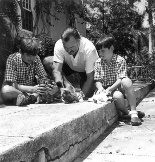 Hemingway and his sons, Gregory and Patrick, playing with the kittens. November, 1946