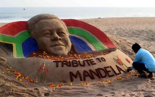 The Indian sand artist Sudarsan Pattnaik lays flowers to the sand figure of Nelson Mandela on the Golden Sea beach in Puri