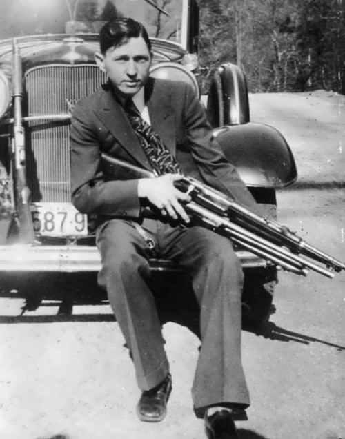 Clyde Barrow holds a rifle and a shotgun, 1933