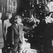 Rockefeller is giving Christmas presents to a group of children